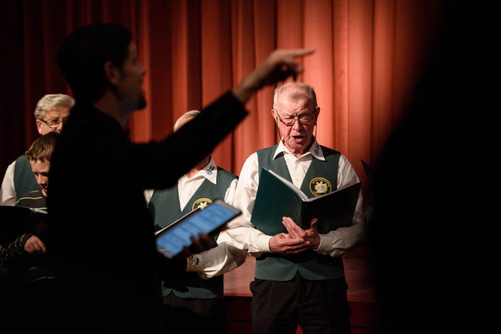 Dirigent Vitali Aleshkevich vor dem Männerchor aus Weixdorf